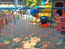 Children Playground in School under Big Tree in Sunny Day Stock Images