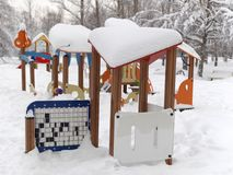 Children Playground In Winter. A children playground in a park covered with massive snow Royalty Free Stock Photo