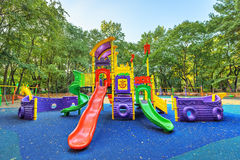 Children playground on yard activities in public park. Children playground on yard activities in public park surrounded by green trees at sunlight morning stock image