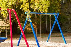 Children playground on yard activities in public park surrounded by green trees at sunlight morning. stock image