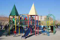 Children on playground. Yerevan, Armenia – March 23, 2014 : This image shows a part of urban life . There are playground in park . Children are playing on Stock Photography