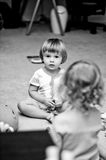 Children playing. A black and white photo of two toddlers playing together on the floor stock photography