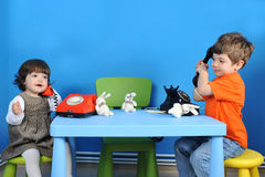 Children playing. Little boy and girl playing with old phones on blue background Stock Images