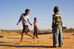Children playing. African children jumping rope in the sand, Mmankodi village Botswana Royalty Free Stock Photos