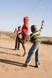 Children playing. African children jumping rope in the sand, Mmankodi village Botswana Stock Photography