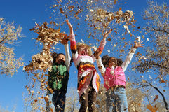 Children Playing. Three children playing in leaves stock images