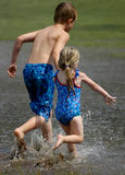 Children playing. A young boy and girl running through puddles splashing stock photo