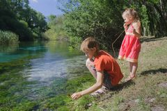 Children playing active game on Tirino river bank in Italian Abruzzo royalty free stock photos