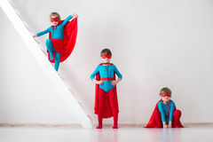 Children playing as superheroes with red coats stock photos