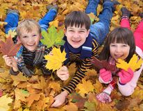 Children playing in Autumn. Happy sister and two young brothers playing in Autumnal leaves outdoors Royalty Free Stock Image