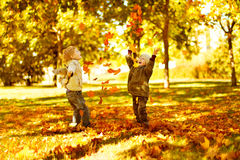 Children playing with autumn fallen leaves in park Royalty Free Stock Images