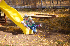 Children playing with autumn fallen leaves in park Royalty Free Stock Photography