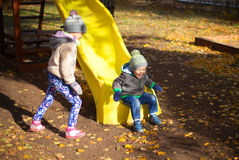 Children playing with autumn fallen leaves in park Stock Image
