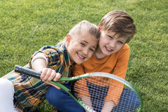 Children playing with badminton racquet while sitting together on grass. Happy children playing with badminton racquet while sitting together on grass royalty free stock photo