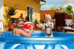 Children playing with ball in water pool Stock Photography