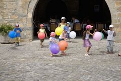 Children playing with balloons on Plaza Mayor, in Ainsa, Huesca, Spain in Pyrenees Mountains, an old walled town with hilltop view Stock Images