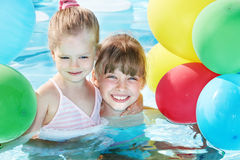 Children playing with balloons in swimming pool. Little girl playing with balloons in swimming pool royalty free stock photos
