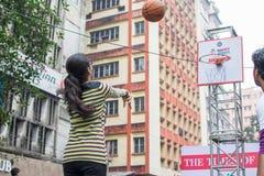 Children playing basket ball at Park Street, Kolkata. KOLKATA, WEST BENGAL, INDIA - JANUARY 17TH 2016 : Unidentified young woman playing basket ball, amongst Stock Photos