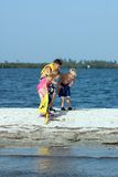 Children playing on beach. Three young children playing on coastal sandbar Royalty Free Stock Image