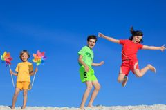 Children playing on beach. Three children playing and jumping on beach against bright blue sky Stock Photos
