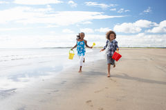 Children playing on beach. Smiling at camera royalty free stock image