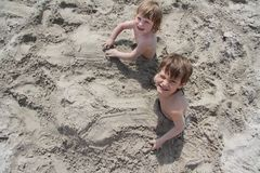 Children playing on beach. Two children in sand on beach Stock Photos