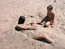 Children playing on beach. Children playing in the sand on beach Stock Image