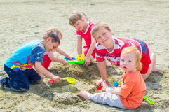 Children on beach. Children playing at the beach digging the sand and building a castle Stock Photos