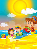 Children playing at the beach having fun by the sea or ocean Stock Image