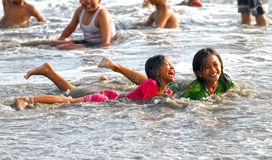 CHILDREN PLAYING AT THE BEACH IN INDONESIA Stock Photos