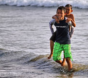 CHILDREN PLAYING AT THE BEACH IN INDONESIA Stock Image