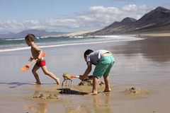 Children playing on the beach. Sand and water royalty free stock image