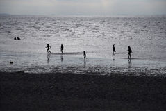 Children playing at the beach in silhouette Royalty Free Stock Photography