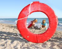 Children playing on beach, view through lifesaver Stock Photo