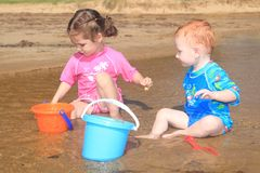 Children playing in beach water with kids toys Stock Images