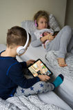 Children playing in bed with their tablets and phones Royalty Free Stock Photography