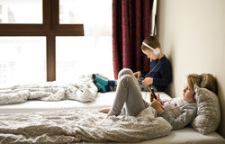 Children playing in bed with their tablets and phones. Two children playing in large bedroom bed next to big window, using their mobile devices such as phones Royalty Free Stock Photos