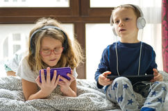 Children playing in bed with their tablets and phones. Two children playing in large bedroom bed next to big window, using their mobile devices such as phones Stock Image