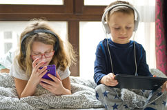 Children playing in bed with their tablets and phones. Two children playing in large bedroom bed next to big window, using their mobile devices such as phones stock photography