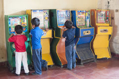 Children playing bingo arcade games. PICHUCALCO, CHIAPAS, MEXICO - DECEMBER 21, 2014: Three young boys entertain themselves by playing old Mexican bingo arcade Royalty Free Stock Photo