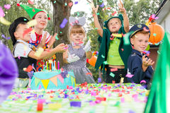 Children playing during birthday party. Children wearing funny costumes during outdoor birthday party Royalty Free Stock Photos