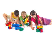 Children Playing With Blocks. Two young boys and a young girl building with multicolor plastic connecting blocks. Isolated on a white background royalty free stock images