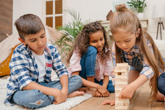 Children playing blocks wood game together at home Stock Photo