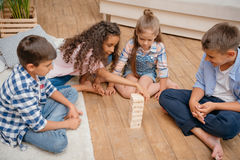 Children playing blocks wood game together at home Stock Photography