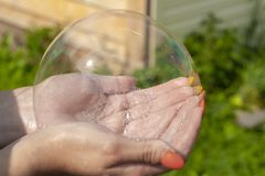 Children playing blow and make soap bubbles, holding a large multi-colored bubble in hand. The concept of children`s holiday