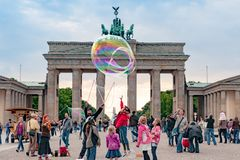 Children playing with blow soap bubbles in front of Brandenburg Gate, Berlin. Children playing with blow Soap bubbles Brandenburg Gate. One Girl jumps to reach stock photos