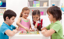 Children playing board game. Sitting around a small table stock photography