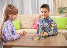 Children playing board game ludo at home on the table Royalty Free Stock Photo
