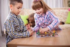 Children playing board game ludo at home on the table Stock Images
