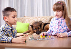 Children playing board game ludo at home on the table Stock Image